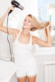 Woman dry hair hairdryer at bathroom Stock Images