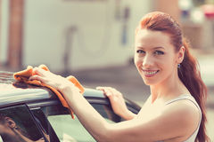 Woman dry wiping car with microfiber cloth after washing it. Young woman dry wiping her car with microfiber cloth after washing it, cleaning auto. Transportation royalty free stock photo