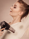 Woman drying armpit with hair dryer Royalty Free Stock Image