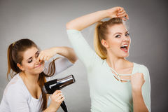 Woman drying friend armpit with hair dryer Royalty Free Stock Image