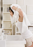 Woman Drying Hair. A woman is drying her hair with a towel in her bathroom.  She is looking in the mirror.  Vertically framed shot Royalty Free Stock Images