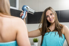 Woman drying hair. Haircare. Beautiful long haired woman drying hair in bathroom Stock Photos