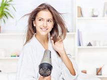 Woman drying hair at home. Young woman drying hair at home Stock Image
