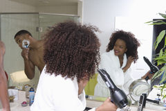 Woman Drying Hair While Man Shaving In Bathroom. African American women drying hair while men shaving in bathroom Stock Photos