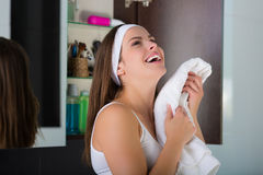Woman drying her face with a towel. Woman with a white towel drying up her face after washing Royalty Free Stock Photo