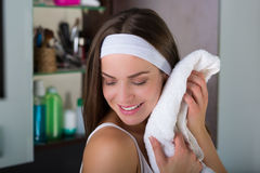 Woman drying her face with a towel. Woman with a white towel drying up her face after washing Stock Images