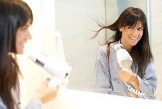 Woman drying her hair. Beautiful young woman looking in mirror while drying her hair Royalty Free Stock Photography