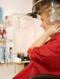 Woman drying her hair. Young woman drying her hair in beauty salon Stock Photos