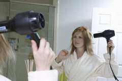 Woman Drying Her Hair In Bathroom. Woman drying her hair in front of mirror Stock Image