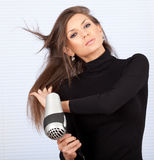 Woman drying her hair by dryer Stock Photography