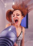 Woman drying her hair. Excited strange woman drying her hair with drier Stock Photography