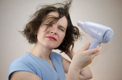 Woman drying her hair. With hairdryer Stock Image