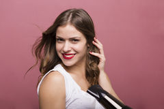 Woman drying her hair. Pretty woman styling her hair with a hairdryer Royalty Free Stock Photos