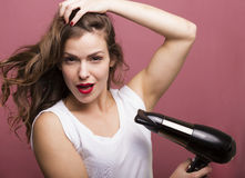 Woman drying her hair. Pretty woman styling her hair with a hairdryer Stock Images