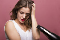 Woman drying her hair. Pretty woman styling her hair with a hairdryer Stock Photos