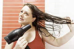 Woman drying her hair. After showering, grooming and hair Royalty Free Stock Images