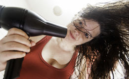Woman drying her hair. After showering, grooming and hair Royalty Free Stock Photography