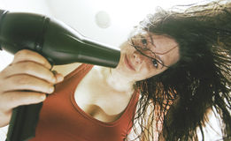 Woman drying her hair. After showering, grooming and hair Stock Image