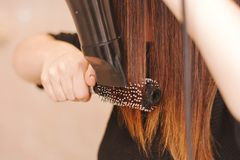 Woman drying her hair. Using a brush and hairdryer Stock Photo