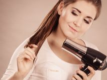 Woman drying her hair using hair dryer. Woman drying her dark brown hair using hair dryer. Studio shot on grey background Stock Photography
