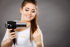 Woman drying her hair using hair dryer. Woman drying her dark brown hair using hair dryer. Studio shot on grey background Stock Photo