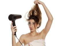 Woman drying her hair. Young beautiful woman drying her hair with a blow dryer on a white background stock images