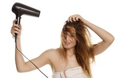 Woman drying her hair. Young beautiful smiling woman drying her hair with a blow dryer on a white background royalty free stock images