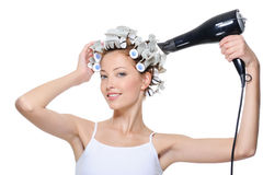 Woman drying her head in hair-curlers Royalty Free Stock Images