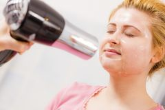 Woman drying her peel off face mask hair dryer. Facial dry skin and body care, complexion treatment at home concept. Woman drying her gel peel off face mask Royalty Free Stock Images