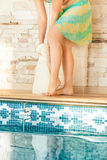 Woman drying legs with towel at swimming pool Stock Photography