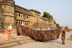 Woman drying them sari in front of Maheshwar palace Royalty Free Stock Photos