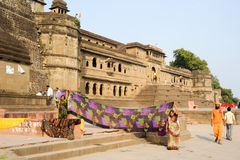 Woman drying them sari in front of Maheshwar palace Royalty Free Stock Photo
