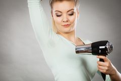 Woman drying armpit with hair dryer Stock Image