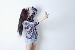 Woman with duck face taking selfie with her smartphone Stock Photos