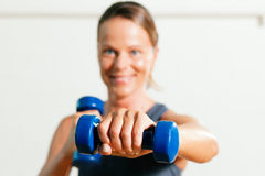 Woman with dumbbell in gym Stock Images