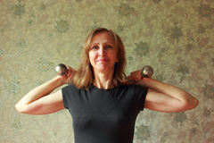 A woman with a dumbbell has been charging Royalty Free Stock Photo