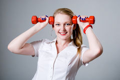 Woman with a dumbbell at the temples Royalty Free Stock Photo