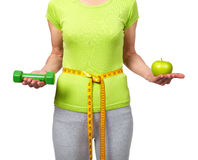 Woman with dumbbells and apple Royalty Free Stock Photography