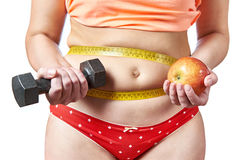 Woman with dumbbells and apple plans diet  and sport Royalty Free Stock Photography