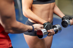 Woman with dumbbells flexing muscles in gym Royalty Free Stock Photo
