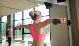 Woman with dumbbells flexing muscles in gym Stock Photos