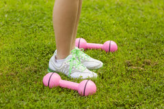 Woman with dumbbells on grass at park Royalty Free Stock Images