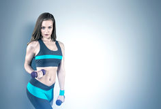 Woman with dumbbells, gray Stock Photography