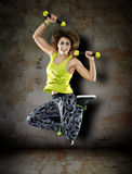 Woman with dumbbells on grunge wall Royalty Free Stock Photo