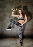 Woman with dumbbells on grunge wall Stock Images