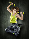 Woman with dumbbells on grunge wall Royalty Free Stock Image