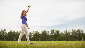 Woman With Dumbbells in a Meadow Royalty Free Stock Images