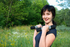Woman with dumbbells outdoors Royalty Free Stock Image