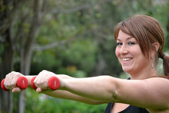 Woman with dumbbells in the park Stock Photography