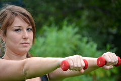 Woman with dumbbells in the park Royalty Free Stock Photography